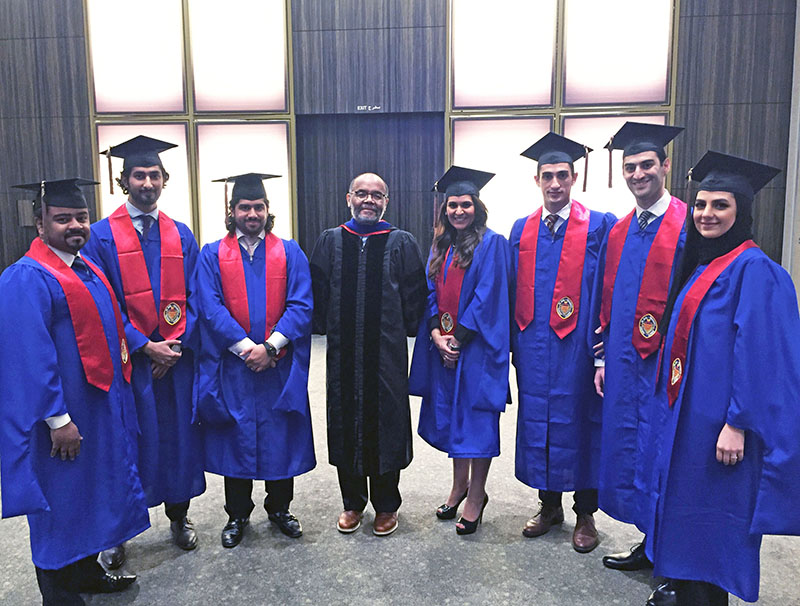Elijah Brewer, chair of the Department of Finance (center), surrounded by members of the DePaul Bahrain program graduating class.