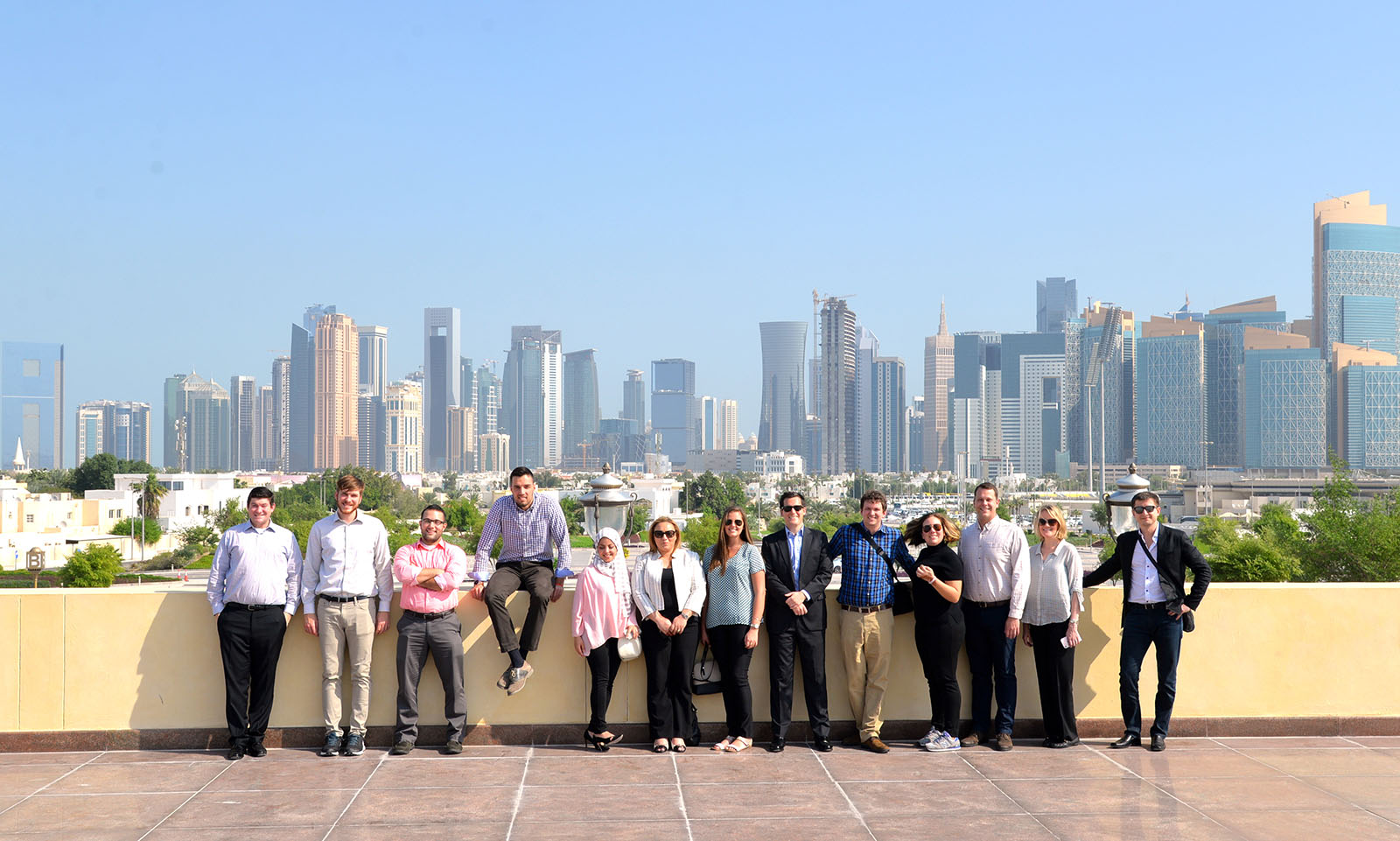 Students pose in front of the Doha skyline.