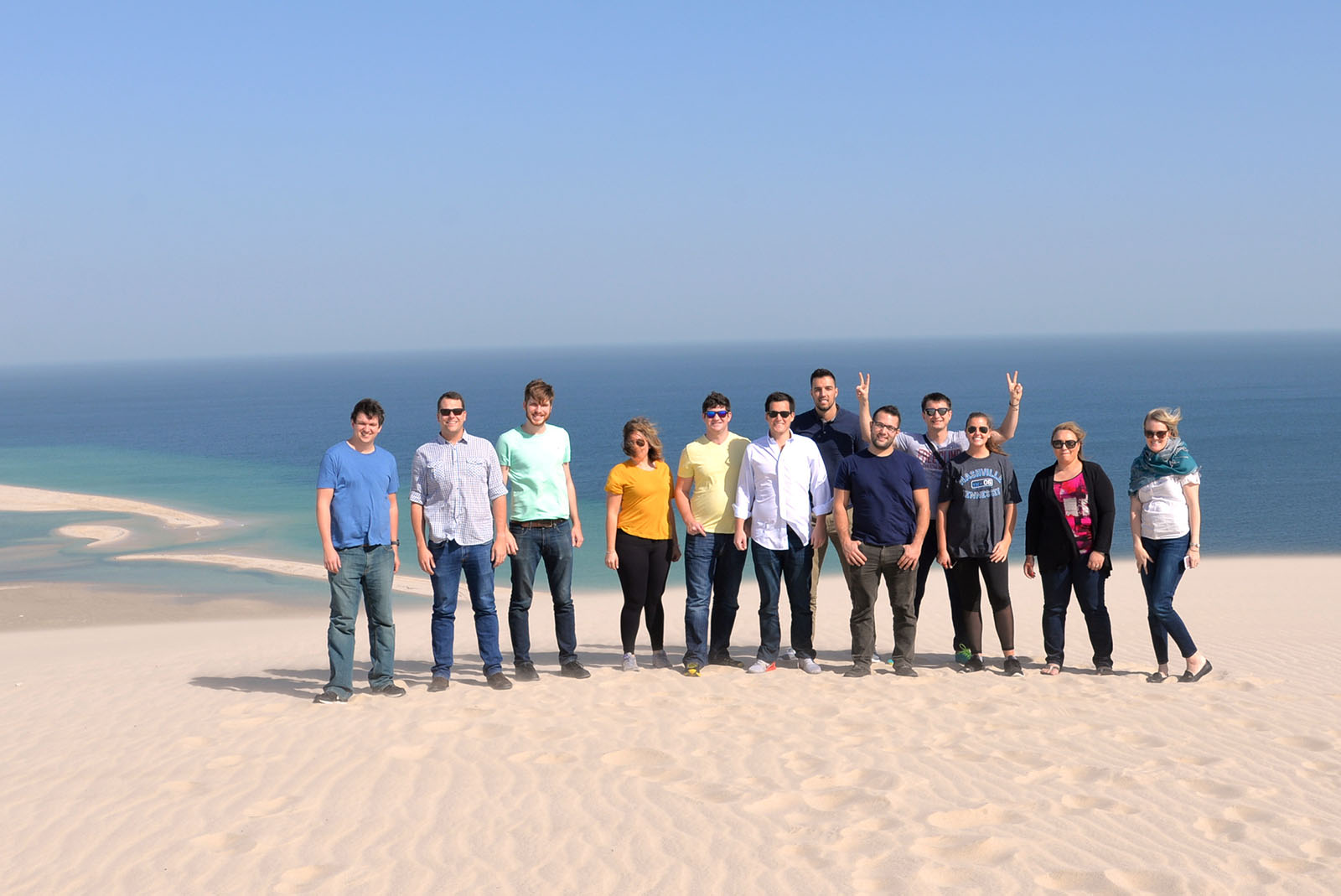 Students stand on one of the towering golden sand dunes in Doha.