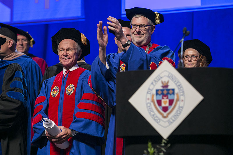 Rick Kash, left, vice chairman of the global consumer information analytics firm Nielsen, and the Rev. Dennis H. Holtschneider, C.M., president of DePaul University, applaud the graduates.