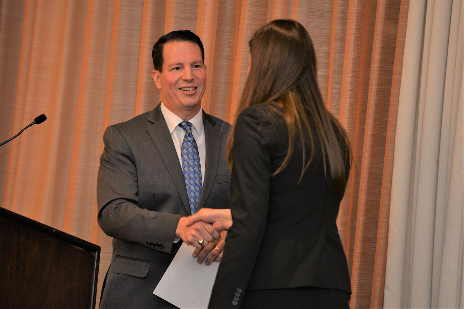 Marketing Associate Professor Rich Rocco hands award to student at Beta Gamma Sigma induction dinner and ceremony