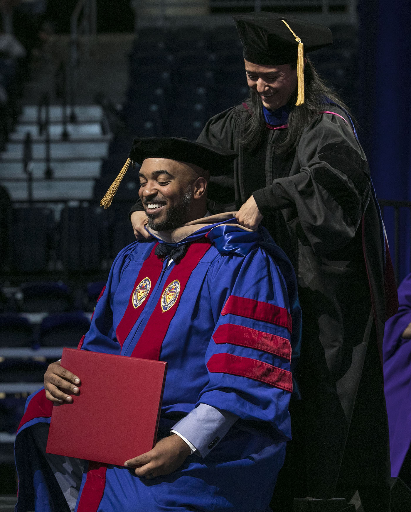 Driehaus College of Business doctoral graduate Brandon Hendrix receives his hood during the DePaul University commencement ceremony.