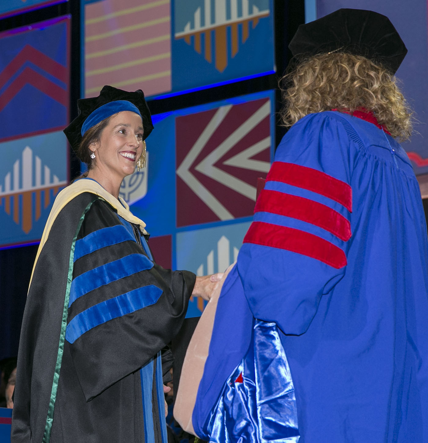 Misty M. Johanson, dean of the Driehaus College of Business, congratulates the graduates as they receive their doctoral degrees at the DePaul University commencement ceremony