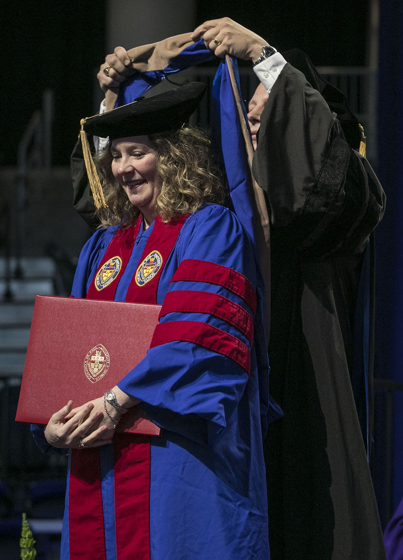 Driehaus College of Business doctoral graduate Tammy Higgins receives her hood during the DePaul University commencement ceremony