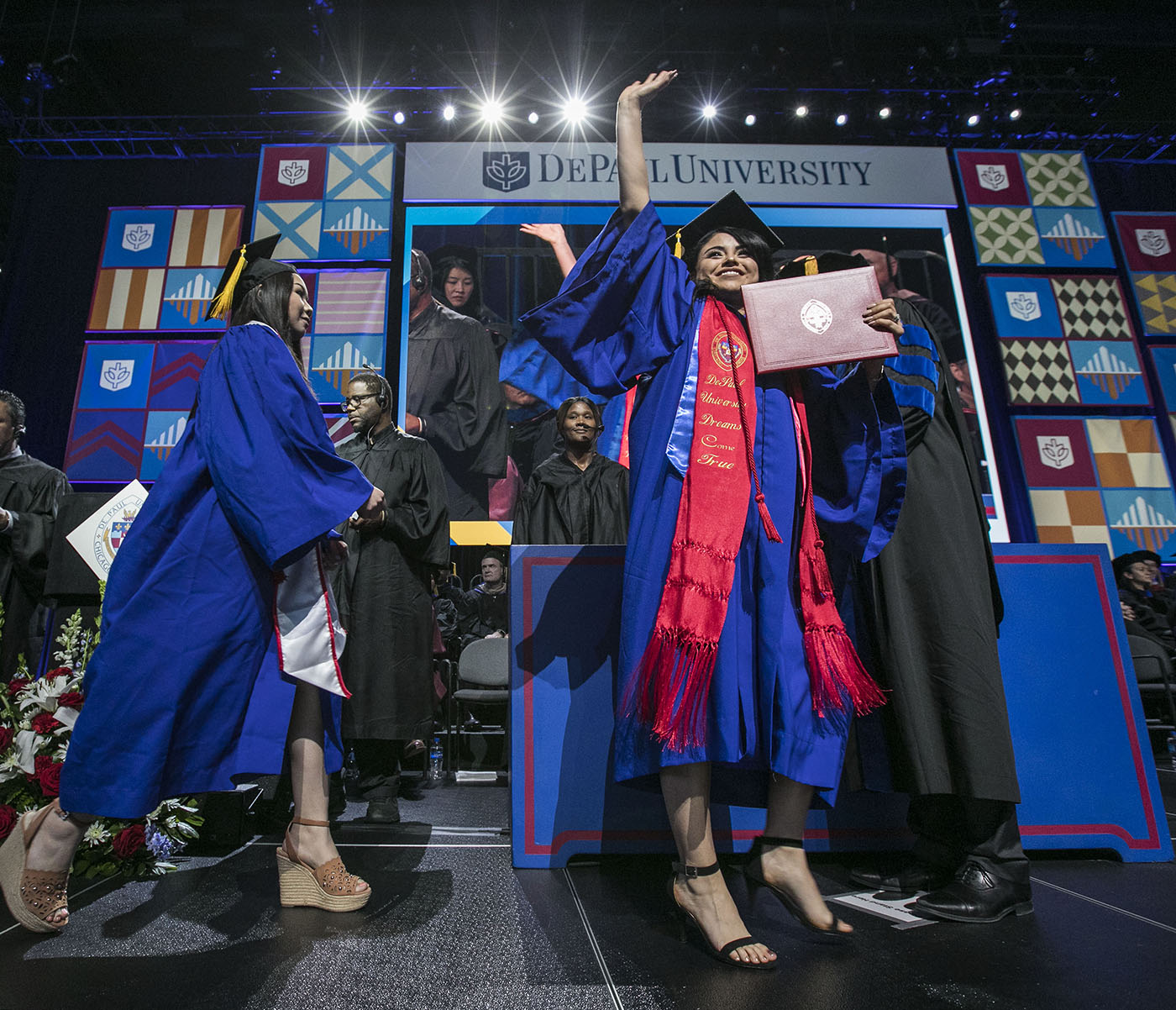 Graduates celebrate as they receive their diplomas during the commencement ceremony for the Driehaus College of Business at the Wintrust Arena
