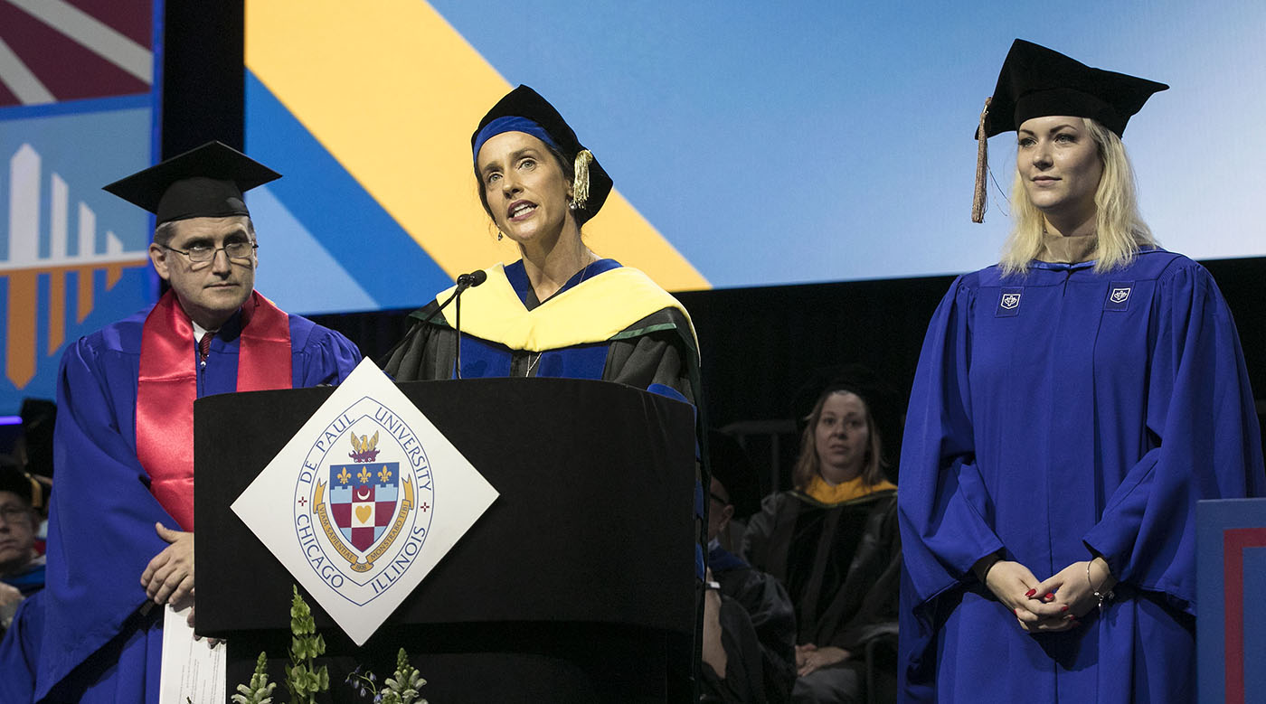 Misty M. Johanson, dean, Driehaus College of Business, center, congratulates the newest alumni members as Paul Sorce, Class of 1991 alumna, left, and Alyssa Poniatowski, Class of 2018 student speaker, listen.