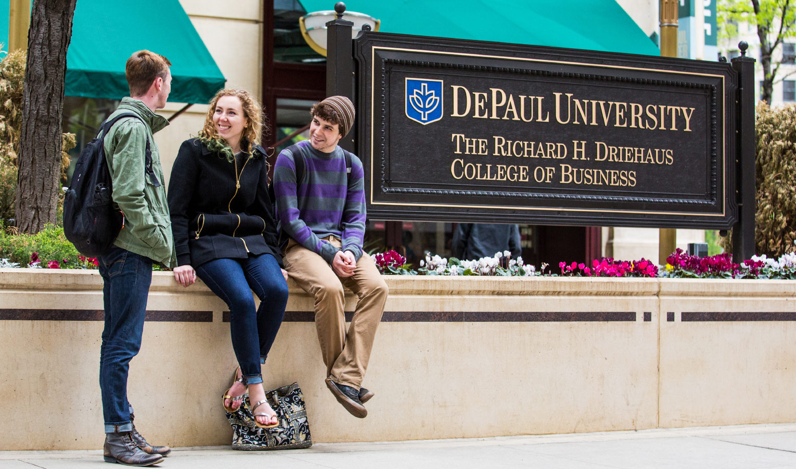 Students sitting near Driehaus College of Business sign